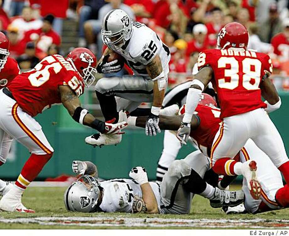 Oakland Raiders running back Justin Fargas (25) leaps over teammate Robert Gallery and through Kansas City Chiefs linebacker Derrick Johnson, left, and DaJuan Morgan (38) as he picks up three yards in the second quarter of a football game Sunday, Sept. 14, 2008, in Kansas City, Mo. (AP Photo/Ed Zurga) Photo: Ed Zurga, AP