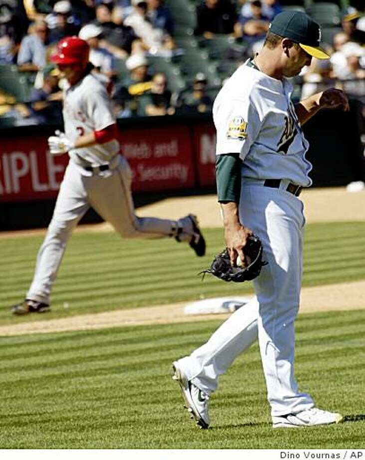 Keith Foulke, right, walks back to the mound after giving up a third home run in a row, this one to the Los Angeles Angels' Brandon Wood, left, in the seventh inning on Thursday, Sept.18, 2008, in Oakland, Calif. Photo: Dino Vournas, AP