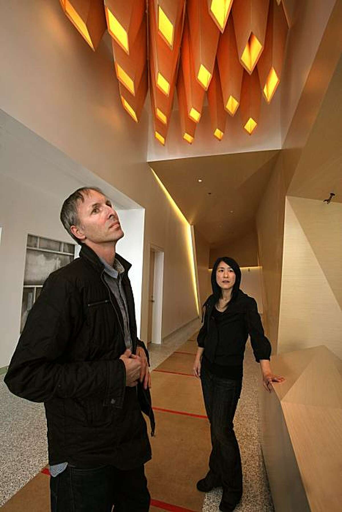 Architects Craig Scott and Lisa Iwamoto have handmade coffered overhead lighting, a custom made desk, and custom made walls with recess lighting in the lobby of their first downtown San Francisco project in progress at One Kearny on Tuesday, March 23, 2010.
