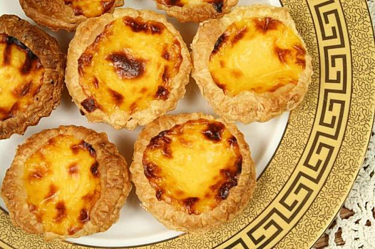 Traditional Portugese pasteis de nata, an irresistible custard pastry, served hot out of the oven.