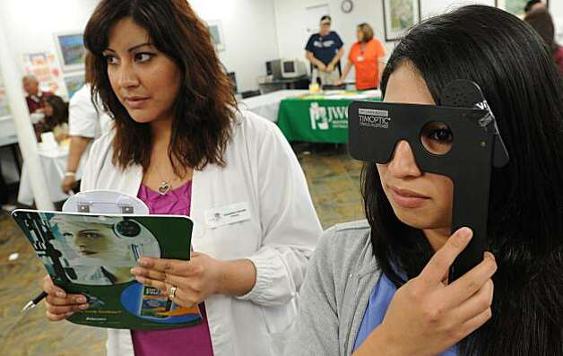Bianca Garcia (R) gets her eyes tested by Alejandra Toscano from South Gate Optometry during a free clinic to provide some healthcare to the one in four Californians who lack health insurance and services, at the ICDC medical training college in Los Angeles on March 24, 2010.  The White House said it was confident President Barack Obama's health reform law had a solid legal foundation after 14 states vowed to challenge it on constitutional grounds. As soon as Obama signed the historic legislation into lawon Tuesday, marking a famous political triumph, the group of state governments which oppose the plan lodged a flurry of legal challenges. Virginia filed suit claiming the health care package violates the US Constitution by requiring every citizen to bu Photo: Mark Ralston, AFP/Getty Images