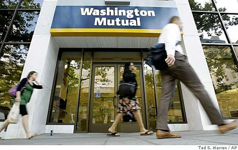 ** FILE ** In this July 15, 2008 file photo, pedestrians walk past a Washington Mutual Inc. branch in downtown Seattle. Ailing Washington Mutual Inc. moved into a better position to find a reprieve or rescue from its mounting loan problems Wednesday, Sept. 17, 2008, after a major investor removed a potential stumbling block to a sale or another infusion of capital. (AP Photo/Ted S. Warren, file) Photo: Ted S. Warren, AP