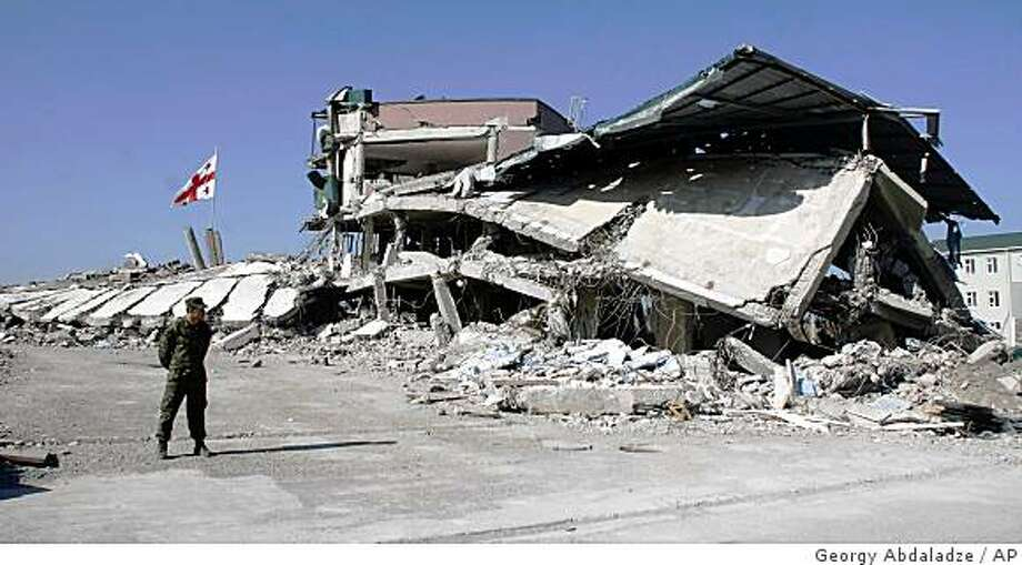 A Georgian soldier is seen next to a destroyed building, at the base of a Georgian brigade that was bombed, during a visit by NATO Secretary-General Jaap de Hoop Scheffer, in Gori, Georgia, Tuesday, Sept. 16, 2008. De Hoop Scheffer came to Georgia with the NATO ambassadors of all 26 allies. On Tuesday, the entire delegation visited Gori, a city targeted by Russian bombs and tanks during the war, which now houses a large tent camp for displaced people. (AP Photo/Georgy Abdaladze) Photo: Georgy Abdaladze, AP