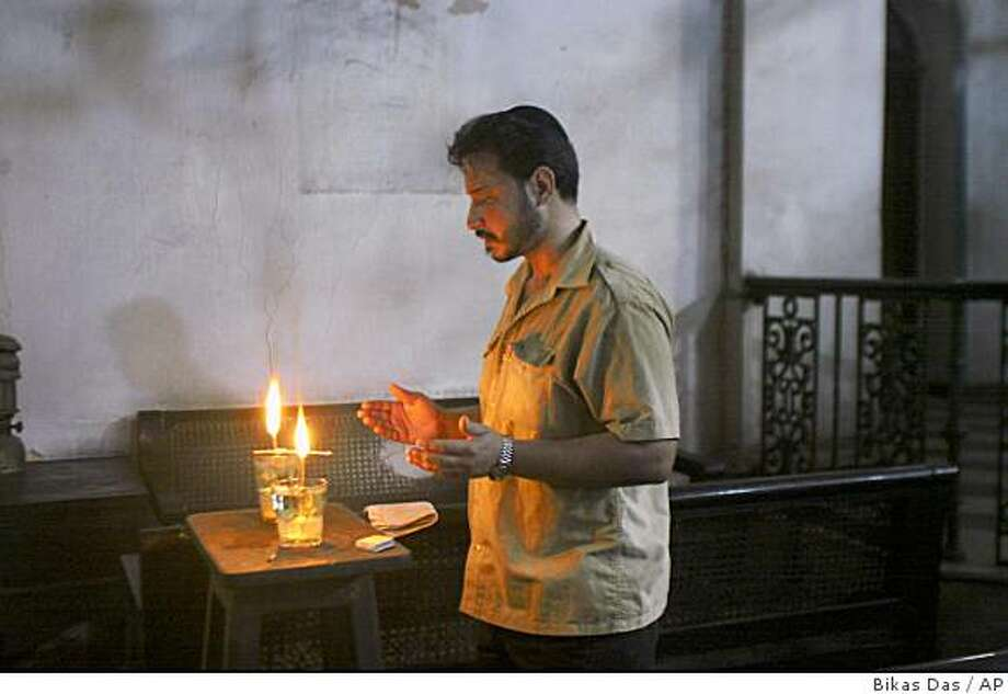 ** ADVANCE FOR SUNDAY, SEPT. 21 ** Shalom Israel, one of the last Jews of Calcutta, lights candles and prays in three existing Synagogues every Friday is shown in Calcutta, India, in this Aug. 8, 2008 photo. In the 1930's and 1940's, Calcutta was a bustling, raucous hub, and Jews formed a solid minority, their wedding parties and religious feasts flowing down the temple steps. There were once 5,000 Jews living in this teeming port city, but now there are fewer than 35. (AP Photo/Bikas Das) Photo: Bikas Das, AP
