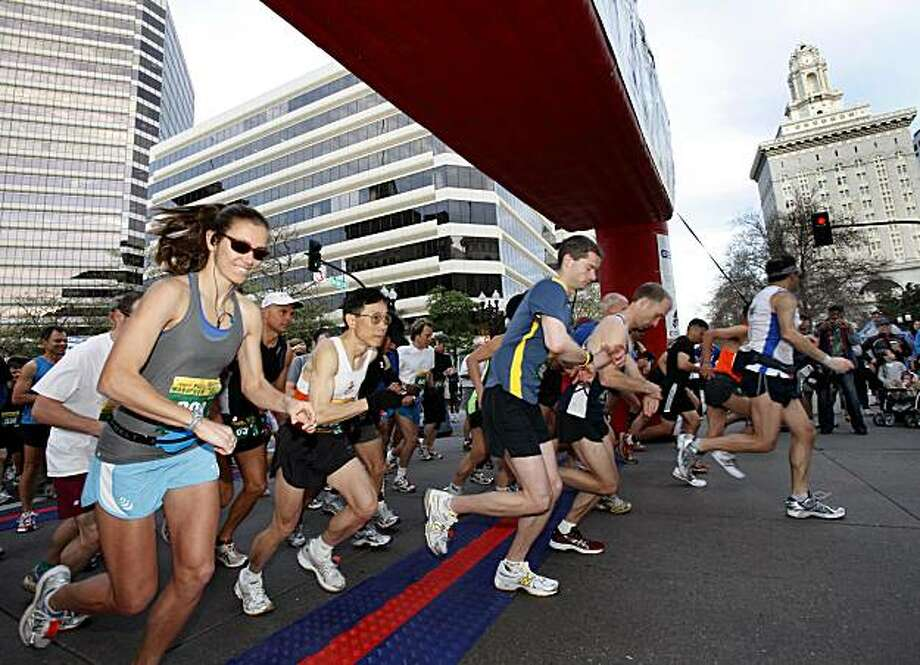 The elite marathoners pass under the starting gate Sunday in Oakland. Photo: Brant Ward, The Chronicle
