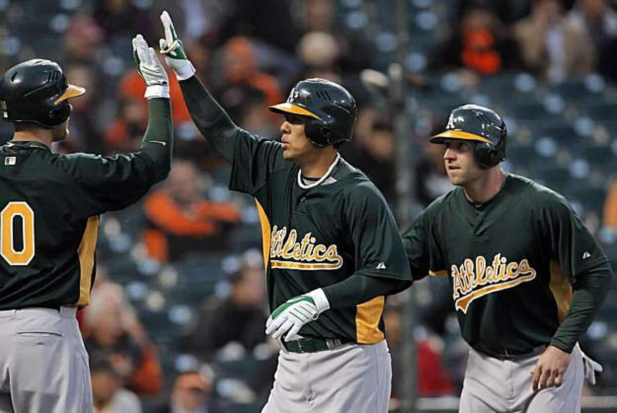 Oakland's Kurt Suzuki celebrates his two-run homerun in the top of the first inning with teammates, Daric Barton, left, and Kevin Kouzmanoff, right. The San Francisco Giants played the Oakland Athletics in a preseason game at AT&T Park in San Francisco, Calif., on Thursday, April 1, 2010.