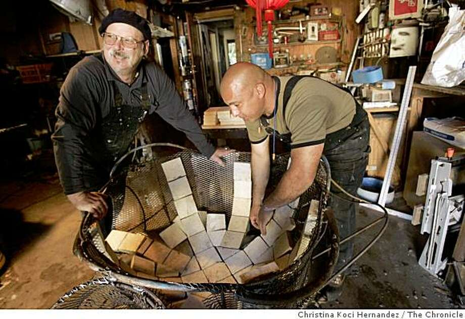 "Artist Dan Macchiarini and (R) Moises Luarte work in Macchiarini's studio in San Francisco as he works on two pieces -- ""The Wave"" and ""Clamshell."" Golden Gate National Recreation Area is working with Burners Without Burners and Surf Rider to create a dozen artistic fire rings that will be installed on Ocean Beach in an effort to contain the popular beach fires to specific locations. Photo: Christina Koci Hernandez, The Chronicle"