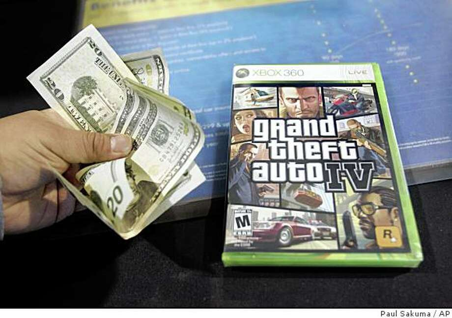 ** FILE ** In this April 29, 2008 file photo, a customer pays cash to purchase the game Grand Theft Auto IV at a Best Buy store in Mountain View, Calif.. Grand Theft Auto IV raked in more than $500 million in its first week in stores, selling more than 6 million units worldwide, said the video game's publisher, Take-Two Interactive Software Inc., on Wednesday, May 7, 2008. (AP Phoito/Paul Sakuma, file) Photo: Paul Sakuma, AP
