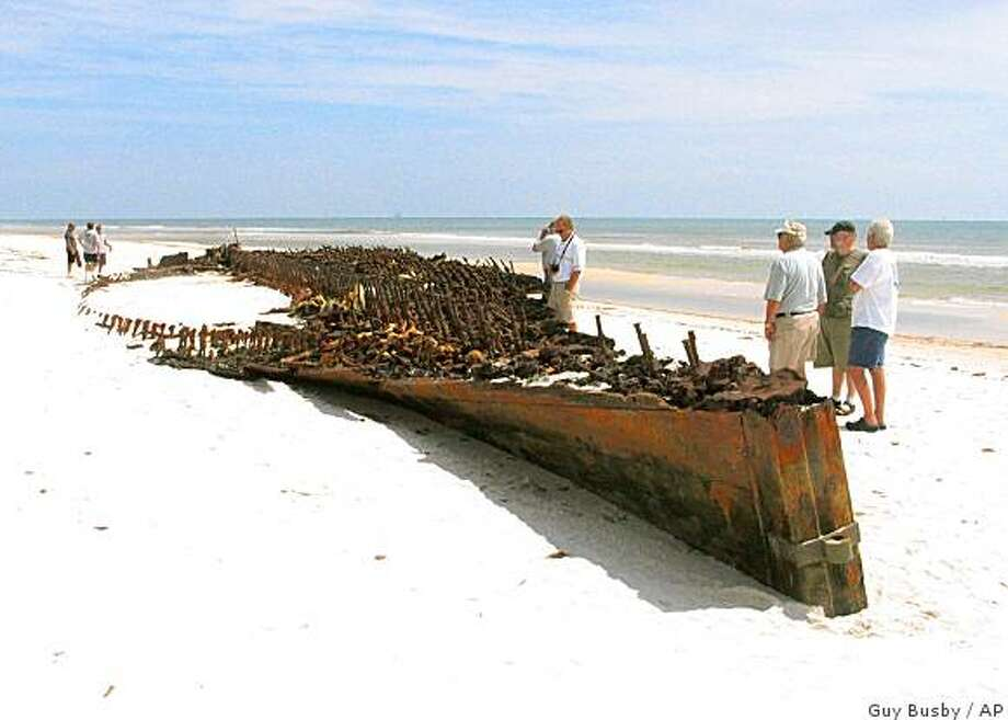 People look over the wreck of a wooden ship uncovered by Hurricane Ike on a beach on Fort Morgan Road in Fort Morgan, Ala., Tuesday, Sept. 16, 2008.  Archeologists say the wreck could be that of a two-masted Civil War schooner that ran aground in 1862 or another ship from some 70 years later. The wreck had already been partially uncovered when Hurricane Camille cleared away sand in 1969. Researchers at the time identified it as the Monticello, a battleship that partially burned when it crashed trying to get past the U.S. Navy and into Mobile Bay during the Civil War. (AP Photo/Press-Register, Guy Busby) ** MAGS OUT, NO SALES ** Photo: Guy Busby, AP