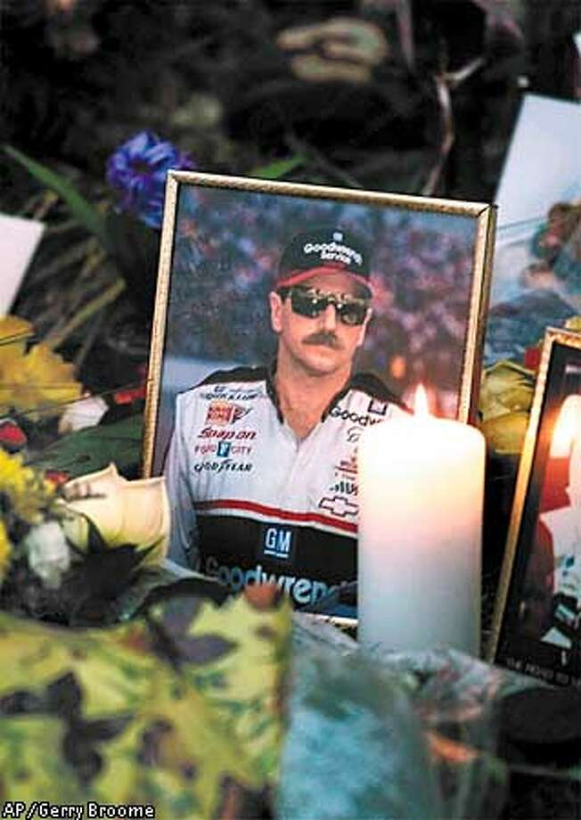A candle burns by a portrait of Dale outside Richard Childress Racing Enterprises Museum in Welcome, N.C., Monday morning, Feb. 19, 2001. The NASCAR champion died from injuries suffered in a last lap crash during the Daytona 500 Sunday. Richard Childress is the No. 3 car owner. (AP Photo/Gerry Broome) Photo: GERRY BROOME