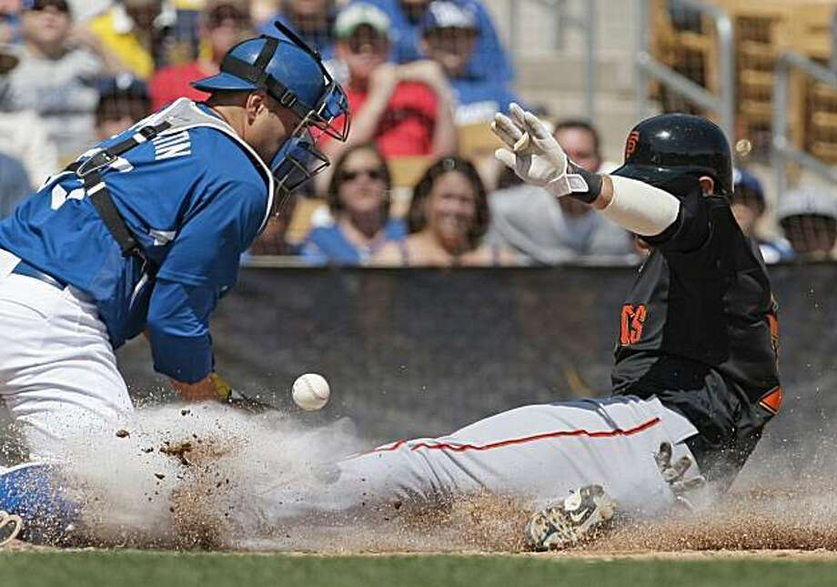 San Francisco Giants' Brandon Crawford slides home safely as Los Angeles Dodgers catcher Russell Martin waits for the throw in the third inning in a spring training baseball game Wednesday, March 31, 2010 in Glendale, Ariz. The Giants won 6-2. Photo: Tony Dejak, AP