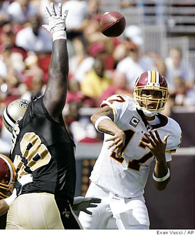 Washington Redskins quarterback Jason Campbell, right, throws past New Orleans Saints defensive tackle Sedrick Ellis, left, during the second quarter of their NFL football game on Sunday, Sept. 14, 2008, in Landover, Md. The Redskins won the game 29-24.  (AP Photo/Evan Vucci) Photo: Evan Vucci, AP