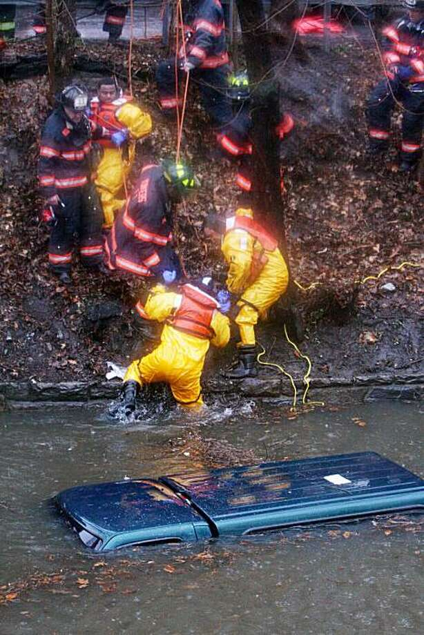 Yonkers, N.Y., firefighter Jerry Thompson is helped out of the water by fellow firefighters after checking a submerged vehicle for occupants on a flooded section of the Bronx River Parkway in Bronxville, N.Y., Tuesday, March 30, 2010. The driver was already pulled to safety. Photo: Frank Becerra Jr, AP