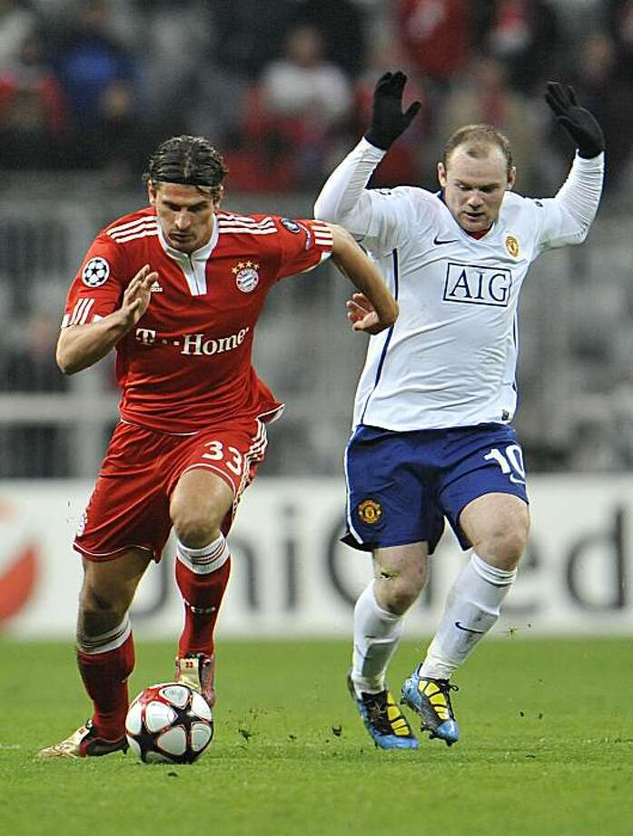 Munich's Mario Gomez, left, fights for the ball with Manchester's Wayne Rooney during the Champions League quarterfinal first leg soccer match  between FC Bayern Munich and Manchester United  in Munich, southern Germany, Tuesday, March 30, 2010. Photo: Kerstin Joensson, AP