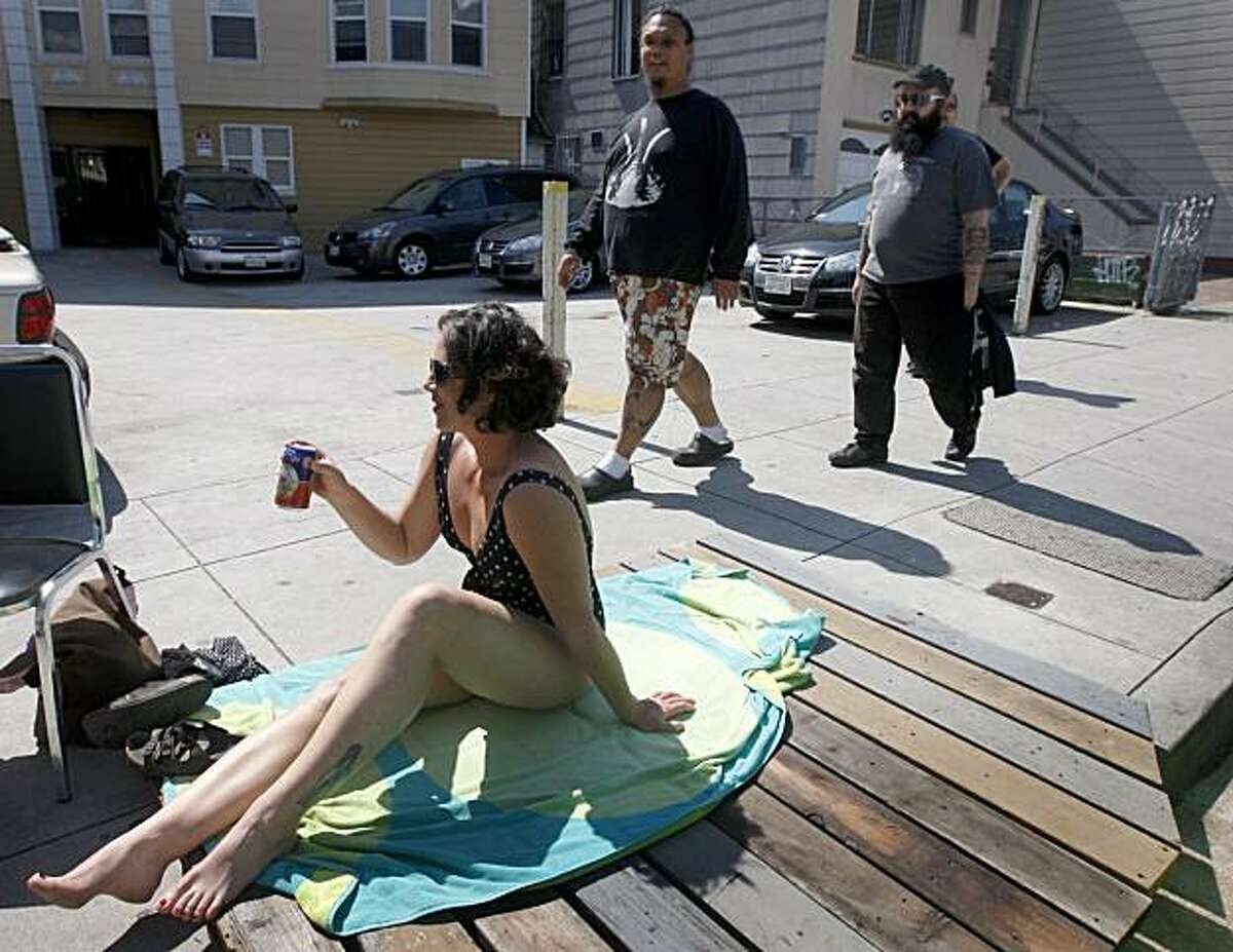 Brooke Cooley enjoys a cold beverage while sunbathing on Cesar Chavez Boulevard near Mission Street in San Francisco on Saturday. Residents upset with a proposed ban on sitting or lying on sidewalks staged events across the city to protest the legislation.