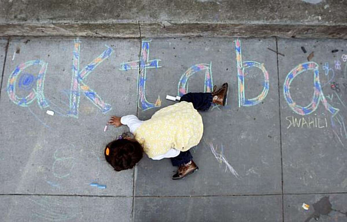 Marina Lombardi, 2, sits on the sidewalk and draws with chalk in front of the Bernal Heights library branch in San Francisco on Saturday. Residents upset with a proposed ban on sitting or lying on sidewalks staged events across the city to protest the legislation.