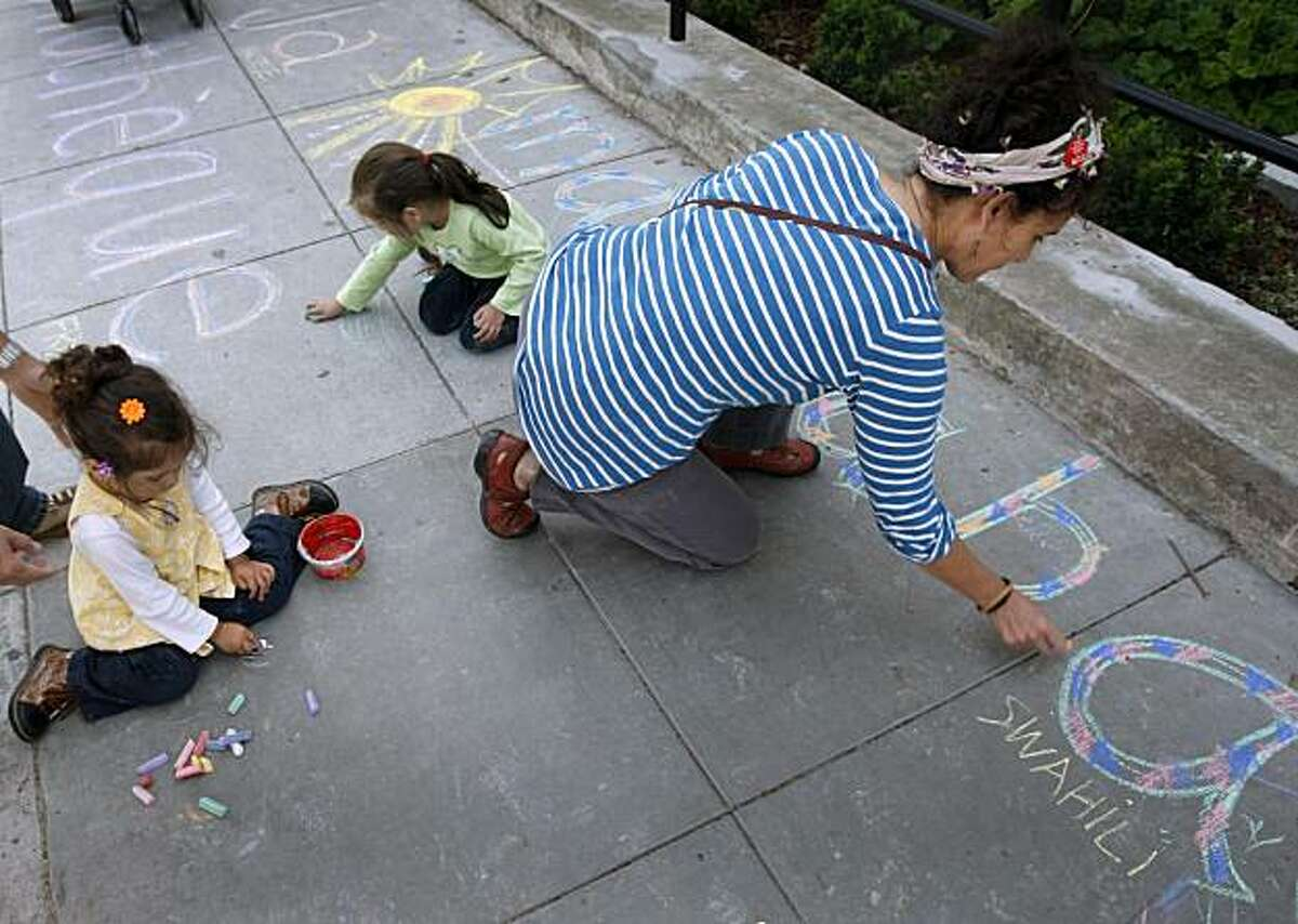 Marina Lombardi, 2, (left) and her sister Isabel, 4, sit on the sidewalk and draw with chalk along with Amy Trachtenberg (right) in front of the Bernal Heights library branch in San Francisco on Saturday. Residents upset with a proposed ban on sitting or lying on sidewalks staged events across the city to protest the legislation.