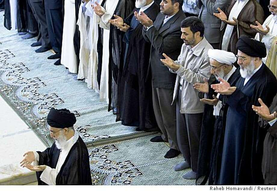 Iran's supreme leader Ayatollah Ali Khamenei (L) and President Mahmoud Ahmadinejad (3rd R) pray during Friday prayers in Tehran September 19, 2008. Khamenei told politicians on Friday to stop squabbling that was undermining the government, in a fresh sign of support for President Mahmoud Ahmadinejad and his cabinet before the 2009 election.    REUTERS/Raheb Homavandi (IRAN) Photo: Raheb Homavandi, Reuters