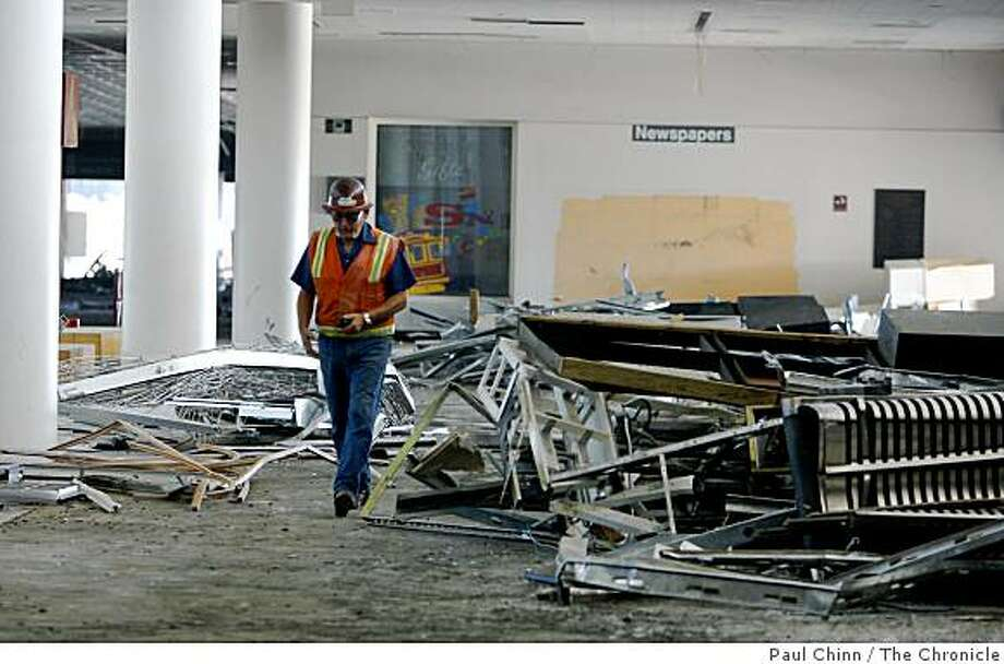 A construction worker walks past debris from demolition work inside Terminal 2 at SFO in San Francisco, Calif., on Thursday, Sept. 18, 2008. Airport officials announced the redesign plans for the former international terminalwhich will be the future home for Virgin America airlines. Photo: Paul Chinn, The Chronicle