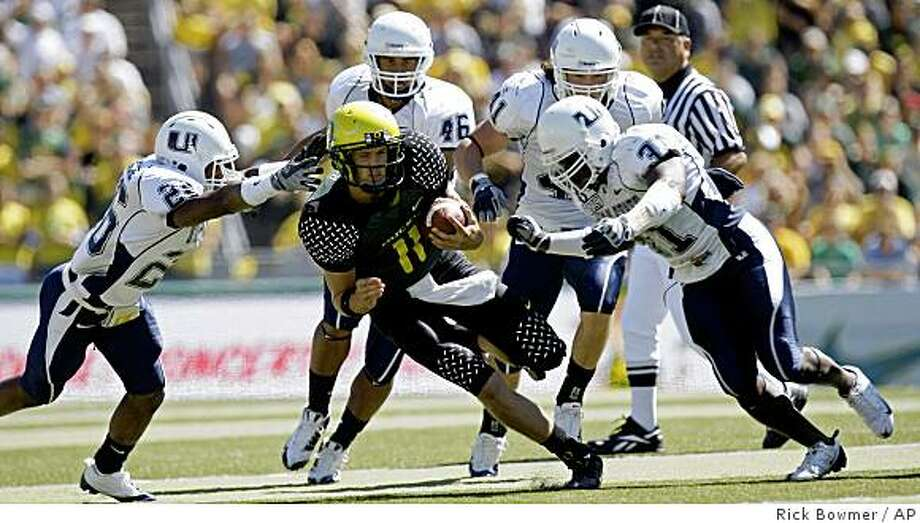 Utah State's Charles Marquise, left, and Paul Igboeli, right, move in to tackle Oregon's quarterback Justin Roper  in the first quarter of their NCAA college football game Saturday, Sept. 6, 2008, in Eugene, Ore. (AP Photo/Rick Bowmer) Photo: Rick Bowmer, AP
