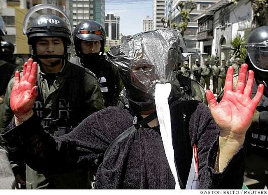 A supporter of Bolivia's President Evo Morales lifts her hands during a protest against the governor of Pando province Leopoldo Fernandez, near the U.S embassy in La Paz September 15, 2008. Clashes between Morales' supporters and opponents killed up to 30 people in Pando province last week as protests flared across the poor nation's eastern lowlands against the president's drive to redistribute land and change the constitution. The woman's red hands represent the hands of Fernandez, whom the protesters say is responsible for the 30 killed in Pando.  REUTERS/Gaston Brito (BOLIVIA) Photo: GASTON BRITO, REUTERS