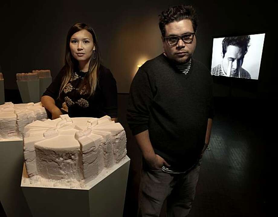 """Artist Kara Tanaka, on Friday Mar. 19, 2010, behind her work, Social Leveler (When Immortality Became Uncouth), 2010 made of sugars, wood and paint, the work was modeled after the process of Promessa, a Swedish method of freeze drying the human body for burial. Fellow artist Marco Rios with his slide and video, a self portrait with waterfalls streaming from his eyes,  Untitled #1, 2010. """"Death's Boutique""""  a joint collaboration between artists Marco Rios and Kara Tanaka at the Yerba Buena Center for the Arts in San Francisco, Calif. Photo: Michael Macor, The Chronicle"""