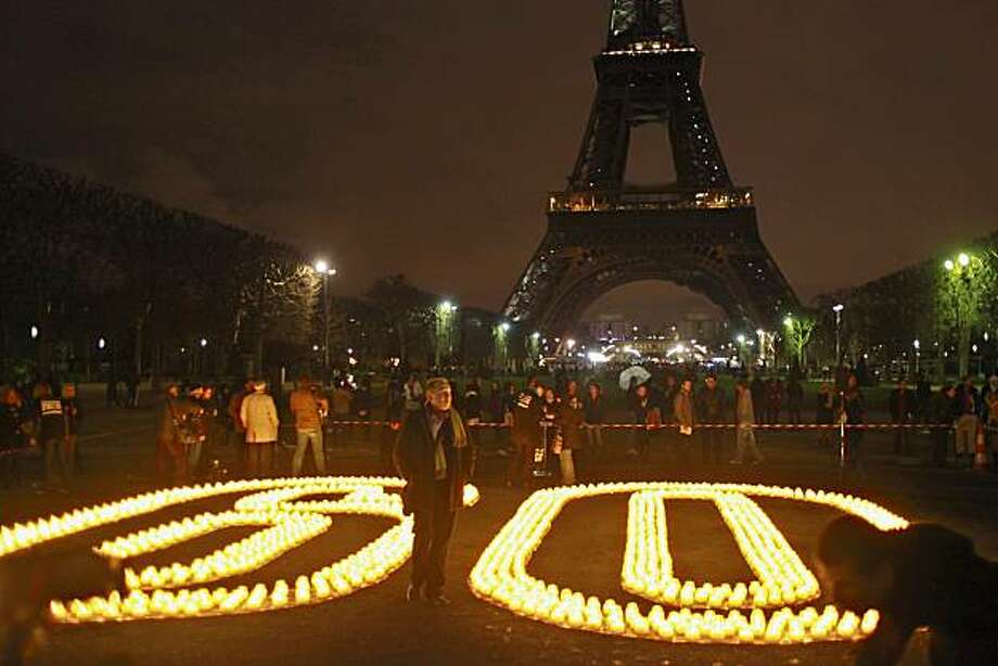 Candle lights are seen in the foreground as the Eiffel Tower is shown just after the 20,000 bulbs illuminating the tower went out, Saturday, March 27, 2010. Many millions of people worldwide are turning off lights and electrical appliances for one hour Saturday night, in a mass gesture to highlight environmental concerns and to call for a binding pact to cut greenhouse gas emissions. Photo: Thibault Camus, AP