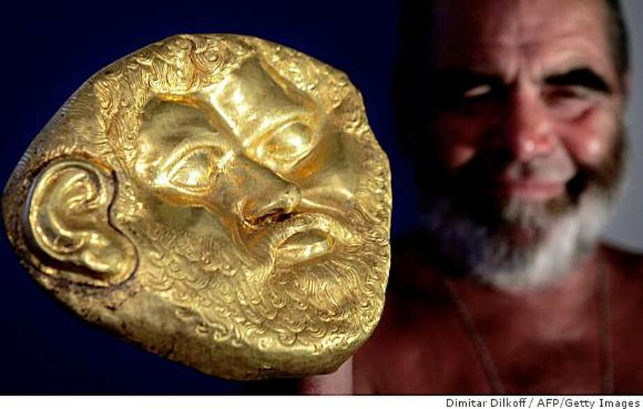 (FILES) This picture taken on August 20, 2004 shows Bulgarian archaeologist Georgi Kitov showing a 2,500-year-old (400-500 B.C.) Thracian mask, weighing 500 grams (more than one pound) of solid gold, in the town of Shipka, 200 kilometers east of the capital Sofia. Kitov, who became world famous with discoveries of treasure-filled Thracian tombs in Bulgaria, died Sunday at age 65, BTA state news agency on September 14, 2008.  AFP PHOTO / DIMITAR DILKOFF (Photo credit should read DIMITAR DILKOFF/AFP/Getty Images) Photo: Dimitar Dilkoff, AFP/Getty Images