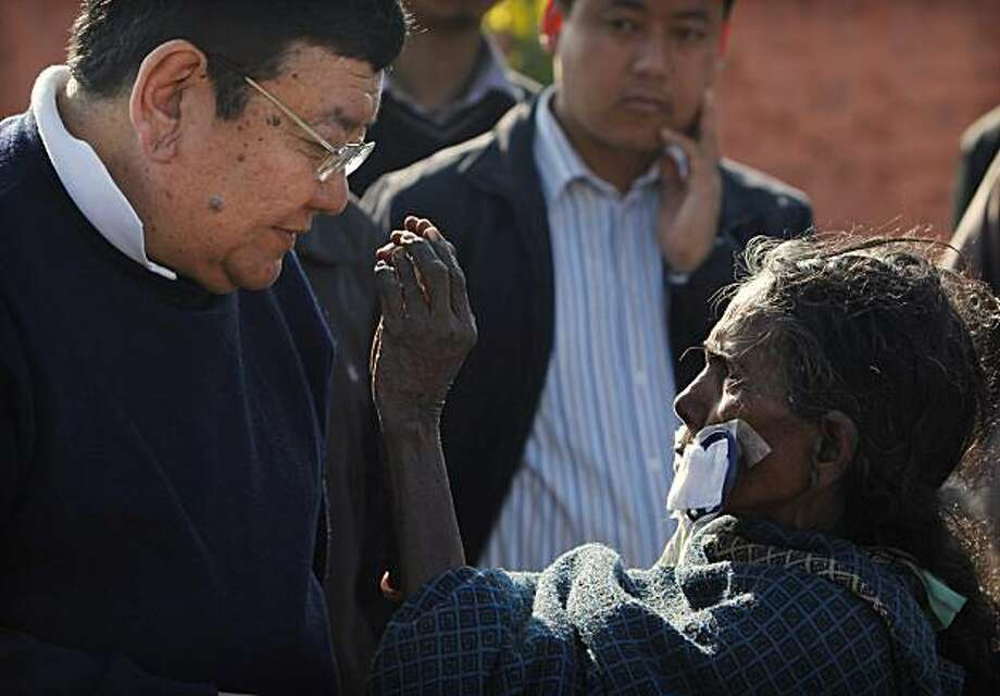 In this Feb. 14, 2010 photograph, Raj Kaliya Dhanuk reaches to squeeze the nose of Dr. Sanduk Ruit to prove that she can see just after her eye patches are removed at Hetauda community eye hospital in Hetauda, about 40 kilometers (18 miles) south of Katmandu, Nepal. Dhanuk and more than 500 others, most of whom have never seen a doctor before, have traveled for days by bicycle, motorbike, bus and even on their relatives' backs to reach Ruit's mobile eye camp. Nepalese master surgeon Ruit estimates sight has been restored to 3-4 million people through his assembly-line approach. Once condemned by the international medical community as unthinkable and reckless, this mass surgery 'in the bush' started spreading from Nepal to poor countries worldwide nearly Photo: Gemunu Amarasinghe, AP