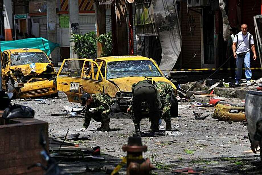 "Colombian soldiers and police officers collect evidence at the site of a bomb attack in Buenaventura, Colombia on March 24, 2010. Five people were killed and 18 wounded after a car bomb exploded near the city hall of Buenaventura, civilian and military sources said. The commander of the Colombian Armed Forces, General Freddy Padilla, initially blamed on the Revolutionary Armed Forces of Colombia (FARC), saying it ""certainly was the FARC"". Buenaventura, one of Colombia's poorest cities, faces daily challenges from rebels, drug traffickers and other criminals. Photo: Luis Robayo, AFP/Getty Images"