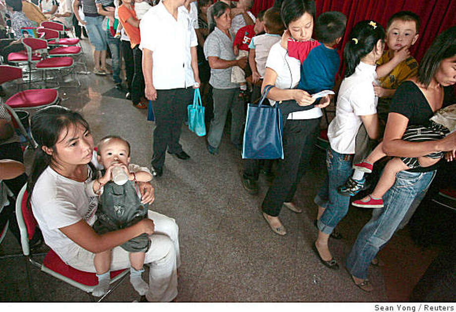 """People wait with their children, who will be undergoing medical checks for possible kidney stones, at a hospital in Nanjing, Jiangsu province, September 18, 2008. China has vowed to overhaul its """"chaotic"""" dairy industry in the wake of a toxic milk scandal that has killed three infants and made thousands more ill, as worried parents flocked to hospitals to have their children examined.    REUTERS/Sean Yong (CHINA) Photo: Sean Yong, Reuters"""
