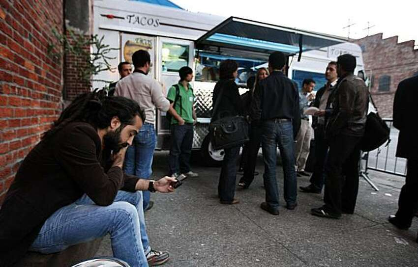 Gercek Karakus from San Francisco checks his E-mail as others stand in line at the taco truck as French entrepreneurs mix with Bay-Area locals at a San Francisco New Tech conference Thursday March 18, 2010. Attracted by Silicon Valley's forward-thinking community, startups from France are quickly moving into the Bay Area. The French-American Chamber of Commerce could soon be the biggest European chamber in Northern California.