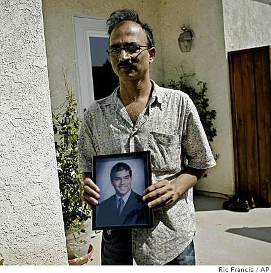 Vijay Vyas holds a photograph of his late son Atul Vyas, 20, Sunday, Sept. 15, 2008, in Simi Valley, Calif., who died in a commuter train crash on Friday. Federal investigators worked Sunday to unravel what caused the collision of a train with a freight locomotive that killed at least 25 people, urging caution as a transit company blamed its own engineer for the horrific accident. (AP Photo/Ric Francis) Photo: Ric Francis, AP