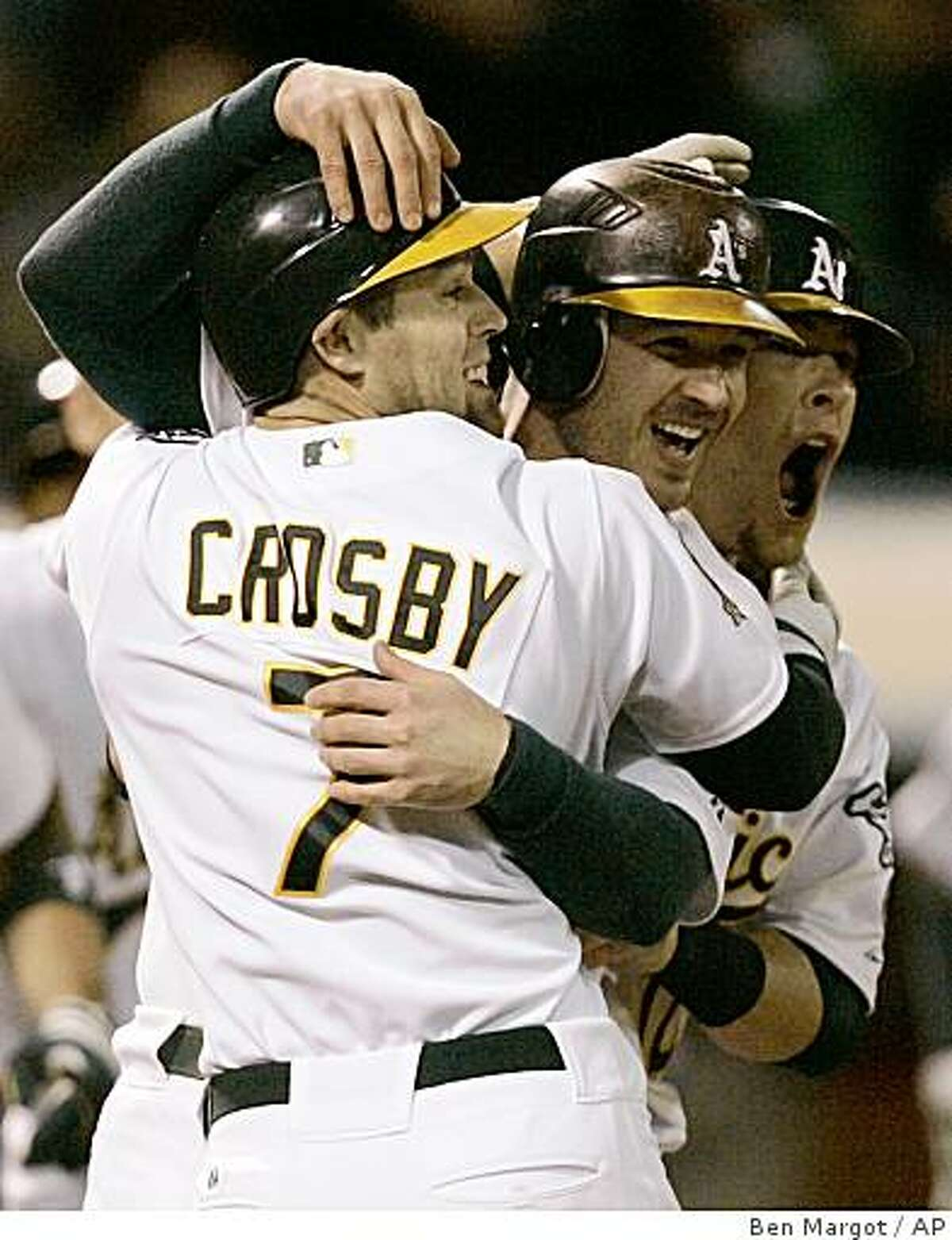 Oakland Athletics' Jack Hannahan, center, celebrates with Bobby Crosby (7) at the end of a baseball game against the Los Angeles Angels, Wednesday, Sept. 17, 2008, in Oakland, Calif. (AP Photo/Ben Margot)