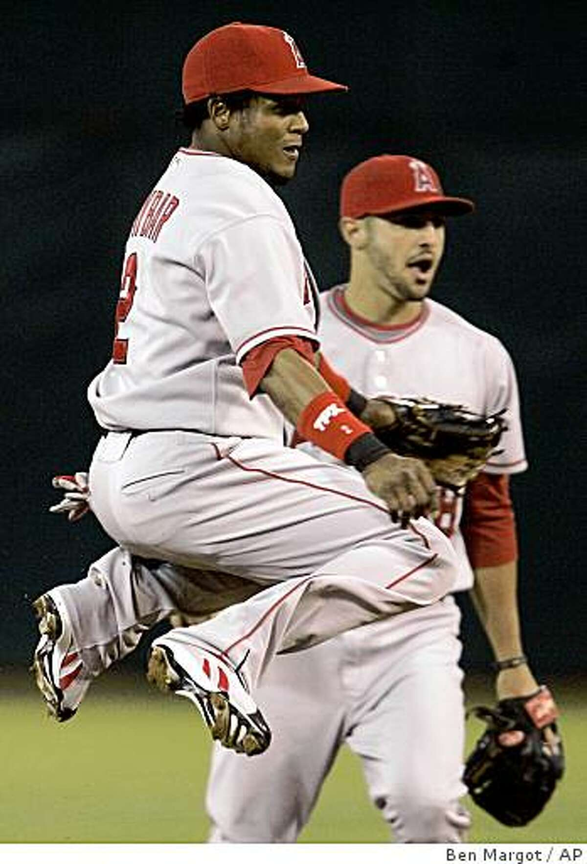 Los Angeles Angels short stop Erick Aybar (2) jumps to avoid Oakland Athletics' Travis Buck (not shown) after completing a double play throw to first base in the first inning of a baseball game, Wednesday, Sept. 17, 2008, in Oakland, Calif. Angels' second baseman Sean Rodriguez, right, backs up the play. (AP Photo/Ben Margot)