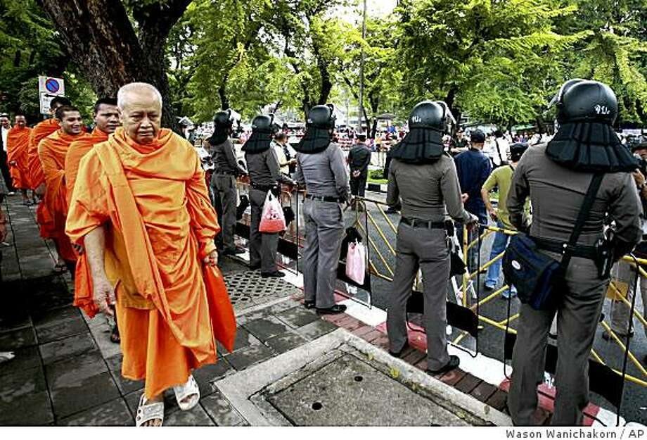 Buddhist monks walk behind riot-police officers standing guard in front of Parliament House in Bangkok, Thailand, on Friday, Sept. 12, 2008. Political allies of Thailand's ousted prime minister deserted him Friday in his bid to return to power in a parliamentary vote, leaving him isolated following his removal by a court for violating conflict-of-interest rules. (AP Photo/Wason Wanichakorn) Photo: Wason Wanichakorn, AP