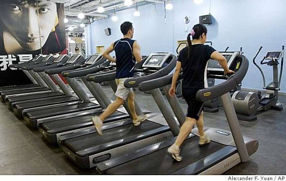 People are shown exercising on running machines at a fitness club in Beijing, China, Wednesday, Sept. 3, 2008.  (AP Photo/Alexander F. Yuan) Photo: Alexander F. Yuan, AP