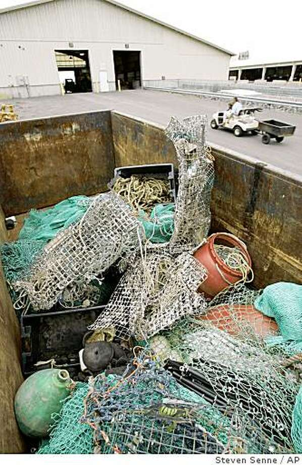 """Lost and abandoned fisherman's gear, including netting, ropes, buoys, and traps, appears in a dumpster at the town dump, in Scituate, Mass., Friday, Sept. 12, 2008. A program introduced in New England this year called """"Fishing for Energy,"""" aims to clean the ocean by collecting every from nylon nets to wooden  lobster traps and burning it to generate electricity. (AP Photo/Steven Senne) Photo: Steven Senne, AP"""