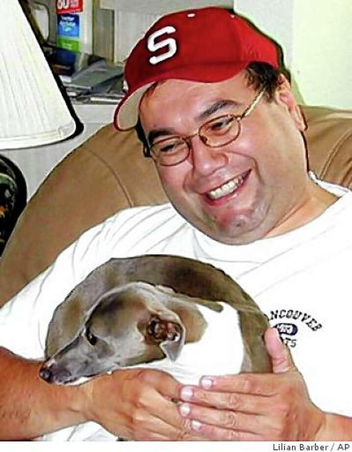 This undated photo released Wednesday, Sept. 17, 2008, courtesy of Lillian Barber, shows Metrolink engineer Robert Sanchez, holding one of Barber's Italian greyhounds.  Sanchez, 46, died in the commuter locomotive that slammed head-on into a freight in Los Angeles Friday, killing 24 passengers and injuring nearly 140. (AP Photo/Courtesy of Lilian Barber)  ** NO SALES ** Photo: Lilian Barber, AP