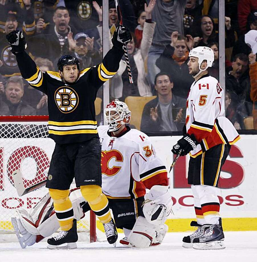 Boston Bruins' Marco Sturm, left, of Germany, celebrates a goal by teammate Dennis Seidenberg, of Germany, in front of Calgary Flames' Miikka Kiprusoff, center, of Finland, and Mark Giordano (5) in the first period of an NHL hockey game, Saturday, March 27, 2010, in Boston. Photo: Michael Dwyer, AP