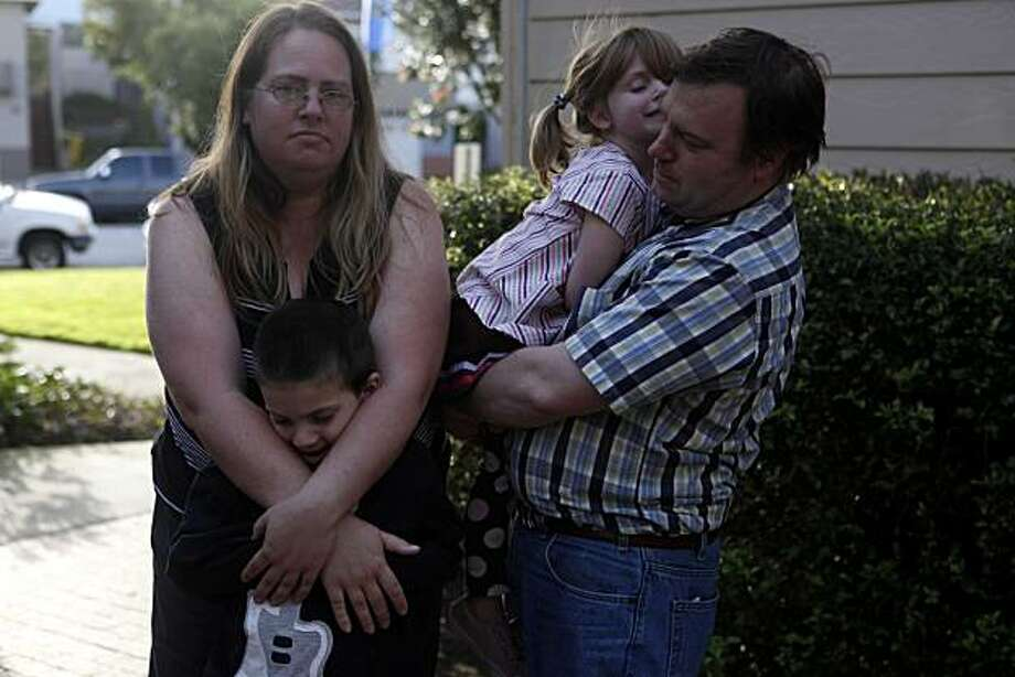 Heather Tanner, laid off from from her lawyering position last summer, stands for a portrait with her husband Carl Tanner and children Joshua, 6, and Natalie, 4, outside their apartment on Friday March 19, 2010 in Pacifica Calif. Heather used to earn $100K per year and now with little prospect of a new job, she says she has resumes out at too many places to count, she and her husband could be facing eviction. Photo: Mike Kepka, The Chronicle