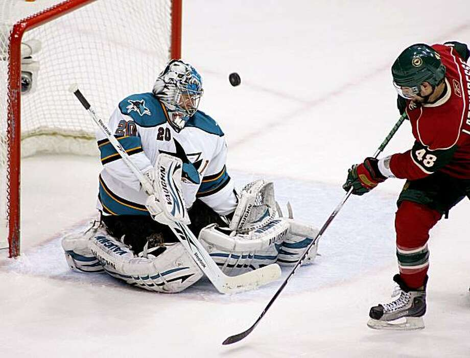 San Jose Sharks goalie Evgeni Nabokov (20) of Kazakhstan deflects a shot by Minnesota Wild left wing Guillaume Latendresse during the third period in the Sharks 4-1 victory over the Minnesota Wild during their NHL hockey game in St. Paul, Minn. Tuesday, March 23, 2010. Photo: Andy King, AP