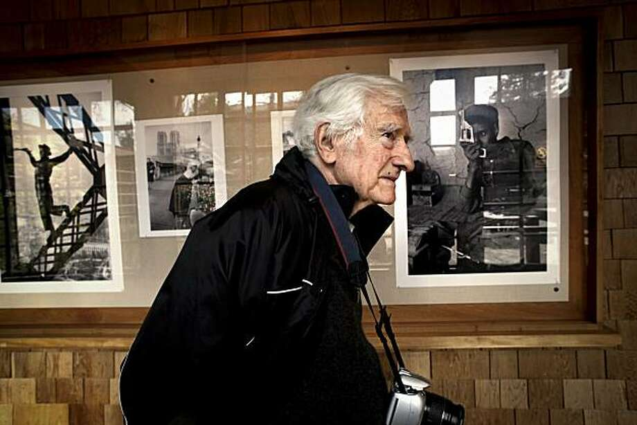 Marc Riboud, the famed French Magnum photographer, on Thursday Mar. 11, 2010, walks past  a few of the prints on display which are part of a retrospective of his work at UC Berkeley's Graduate School of Journalism,  in Berkeley, Calif. Photo: Michael Macor, The Chronicle