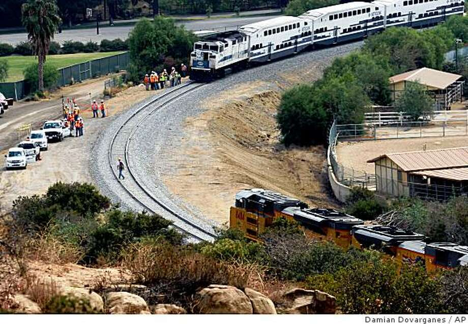 Investigators with the National Transportation Safety Board use stand-in engines to conduct a test on Tuesday, Sept. 16, 2008, to determine when the engineers of two trains were able to see each other in the moments before a head-on crash that killed at least 25 people in Chatsworth, Calif. last Friday. (AP Photo/Damian Dovarganes) Photo: Damian Dovarganes, AP