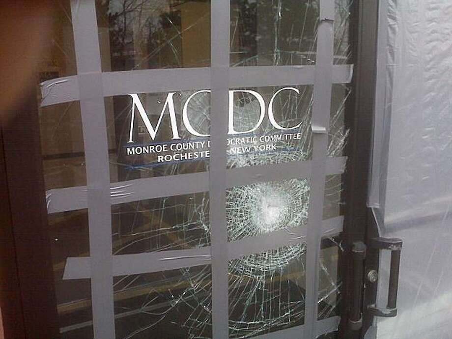 "This picture provided on Wednesday, March 24, 2010 by the Monroe County Democratic Committee in Rochester, N.Y. shows damage to their office after a glass door was struck with a brick with a note reading ""Exremism in Defense of Liberty Is no Vice"" sometime from late Saturday, March 20, 2010 or Sunday, March 21, 2010. Bricks have been hurled through Democrats' windows, a propane line was cut at the home of a congressman's brother and lawmakers who voted for a federal health care bill have received phone threats in the days before and after passage of the sweeping legislation. Photo: AP"