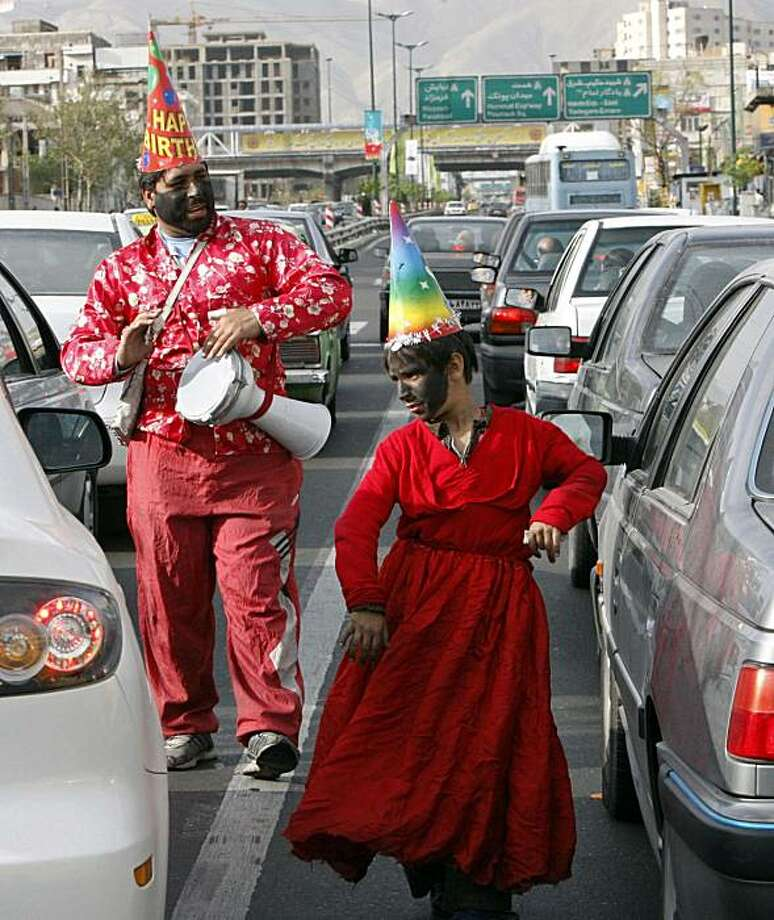 A boy wearing a red robe and black face as a character of the Iranian New Year called Haji Firouz, performing for alms from the car drivers, as a man plays music and sings in the background, along a highway in Tehran, Iran, Friday, March 19, 2010.  The Iranian New Year, or Nowruz, is a 13-day holiday celebrating the arrival of spring and the beginning of the new year on the Persian calendar which starts on March 21. Photo: Vahid Salemi, AP