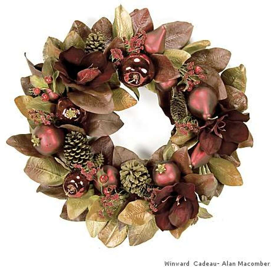 """Made of very realistic faux blossoms and leaves, with berries and holiday fruit ornaments, this stunning 22-inch wreath would normally retail for $80, on sale at our inventory liquidation event for half off of wholesale at $20Holiday magnolia & amaryllis wreath, 22 inch with """"faux"""" magnolia foliage, amaryllis blossoms in deep burgundy tones, fruit ornaments, glitter gypsophelia clusters, and real pine cones. Photo: Winward Cadeau- Alan Macomber"""