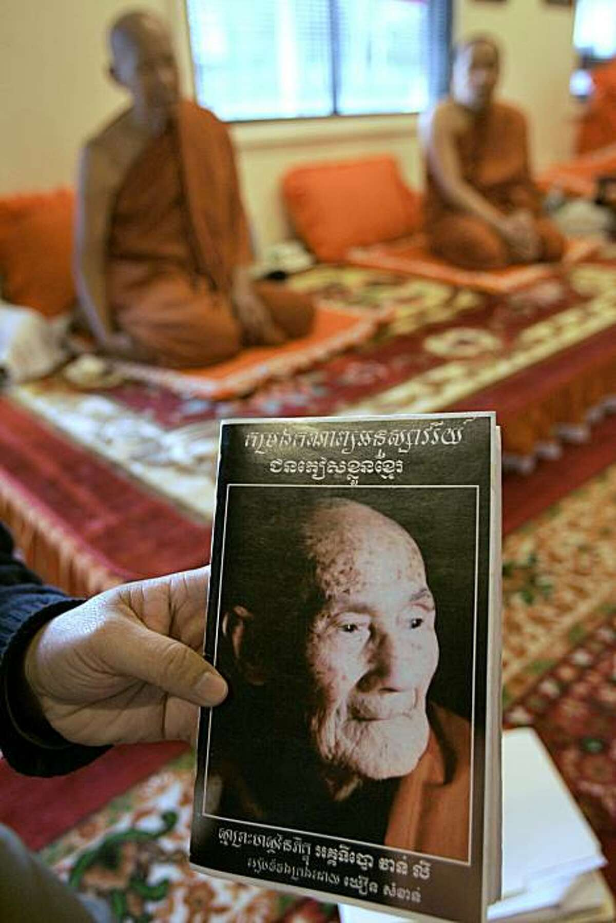 FILE - In this Nov. 20, 2008 file photo, Samkhann Khoeun holds at the Glory Temple, in Lowell, Mass., a Khmer language manuscript of poetry by the Buddhist monk Ly Van Aggadipo that features his photo on the cover. On April 1, 2010, friends and followerswill release a bilingual edition that includes an English translation of his poetry.