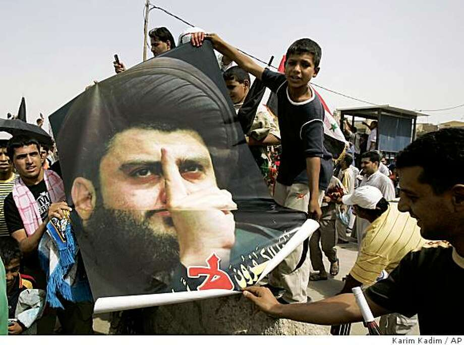 Iraqis dipslay a poster of a powerful Shiite cleric Muqtada al-Sadr during an anti occupation protest in the Shiite enclave of Sadr City in Baghdad, Iraq, Friday, Sept. 12, 2008.  (AP Photo/Karim Kadim) Photo: Karim Kadim, AP