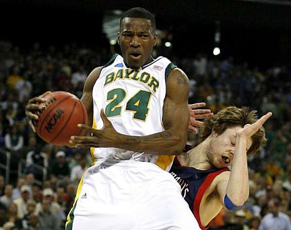 Baylor guard LaceDarius Dunn pulls down a rebound in front of Saint Mary's guard Matthew Dellavedova during first half of the 2010 NCAA South Regional semifinal college basketball game at Reliant Stadium on Friday in Houston. Photo: James Nielsen, Chronicle